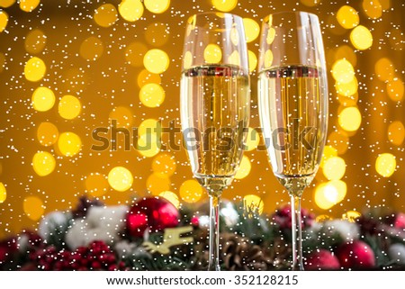 Two champagne glass on christmas bokeh background with snow