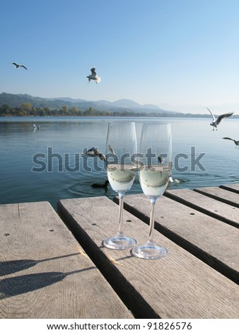 Two champagne glasses against a lake