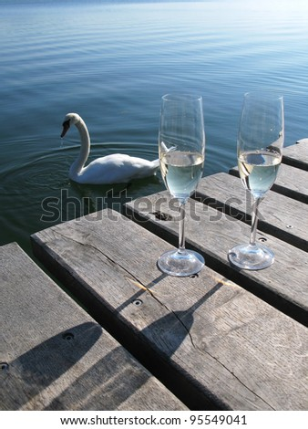 Two champagne glasses against a lake - stock photo