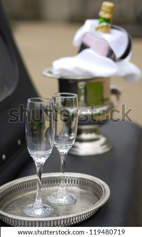 Two Champagne glasses and bottle on ice at wedding. - stock photo