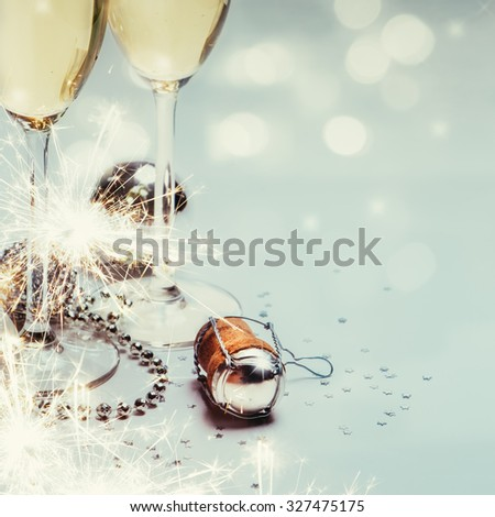 Two champagne glasses and cork with baubles, sparklers, confetti and lights. Copy space. - stock photo