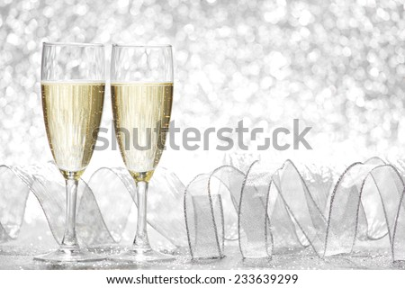 Two champagne glasses and decoration on silver bokeh background - stock photo