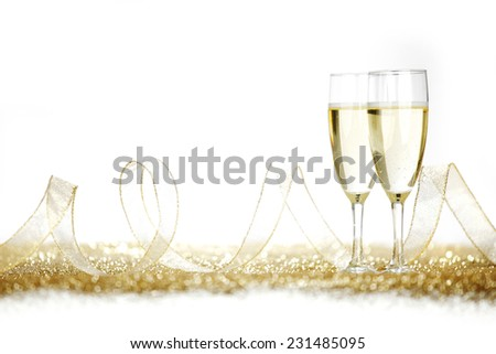 Two champagne glasses and golden shiny glitters isolated on white background - stock photo