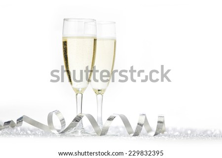 Two champagne glasses and silver shiny glitters isolated on white background - stock photo