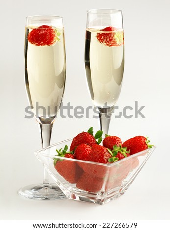two champagne glasses and strawberries on white background - stock photo