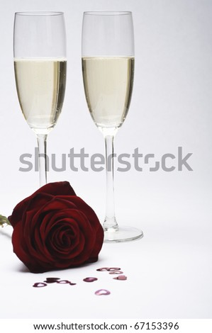 Two champagne glasses (flutes) have focus, with dark red rose and a scattering of heart confetti in soft-focus in the foreground. - stock photo