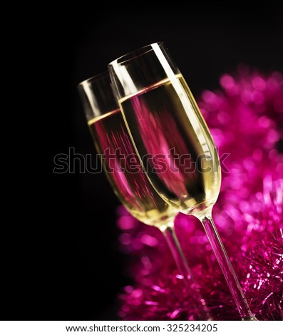 Two champagne glasses in front of purple sparkling background - stock photo