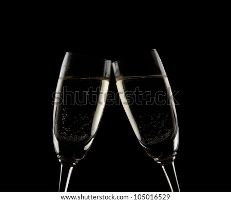 Two champagne glasses in toasting isolated on black - stock photo
