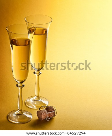 Two champagne glasses isolated on a yellow. - stock photo