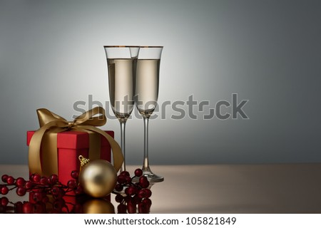 Two champagne glasses on a golden surface decorated with a present and Christmas bauble