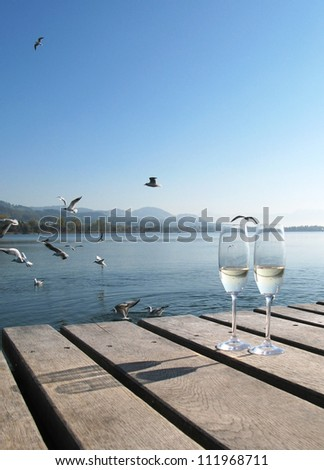 Two champagne glasses on a wooden jetty - stock photo