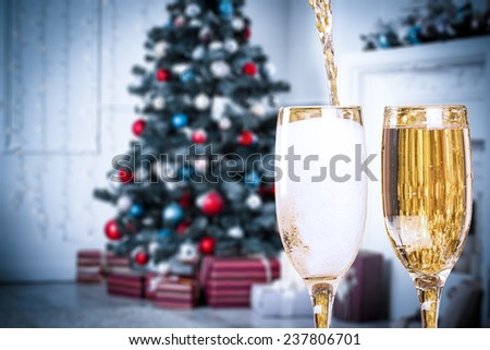 Two Champagne Glasses On Defocused Background Living Room With Christmas Tree. Blue toned - stock photo