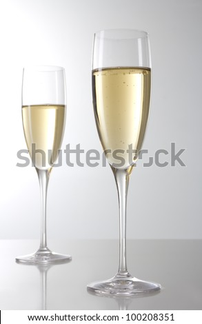 Two champagne glasses on grey