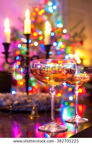 Two champagne glasses on illuminated christmas tree defocused background. Multicolored vibrant vertical image. - stock photo