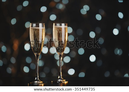 Two champagne glasses over dark bokeh background