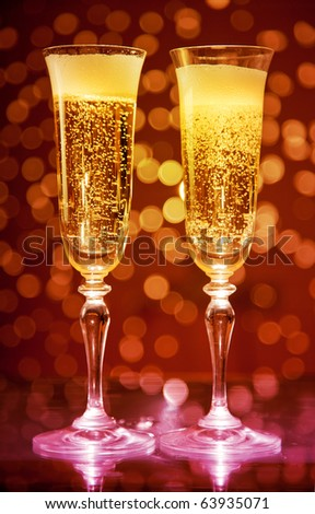 Two champagne glasses over holiday bokeh background - stock photo