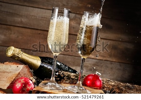 Two champagne glasses pouring on wooden background