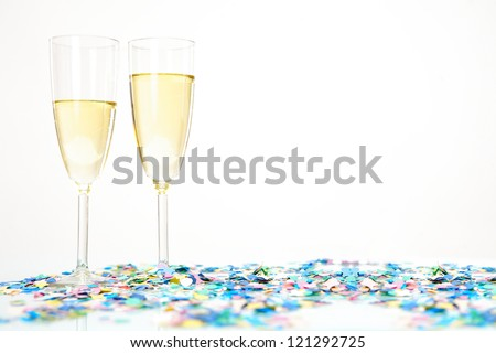 Two champagne glasses with alcohol and colored confetti decoration isolated on white background. Possible copy space - stock photo