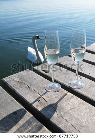 Two champaigne glasses on a wooden jetty against a swan - stock photo