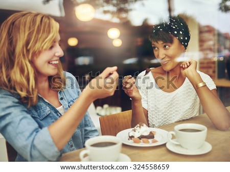 Two charismatic multi ethnic young girl friends sit at a counter in a cafe enjoying a cup of coffee while laughing and chatting - stock photo