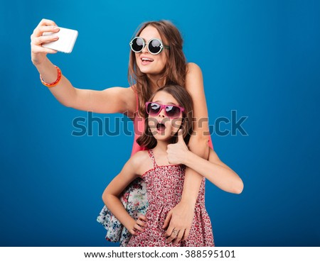 Two charming happy sisters in sunglasses taking selfie using smartphone over blue background - stock photo