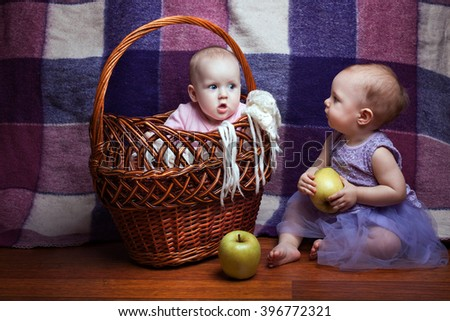 Two charming little girls. One girl sitting in a basket, the second girl sitting beside her and holding an apple - stock photo