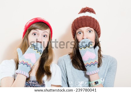 two charming young women in winter caps gloves puzzled looking in camera on white background portrait - stock photo