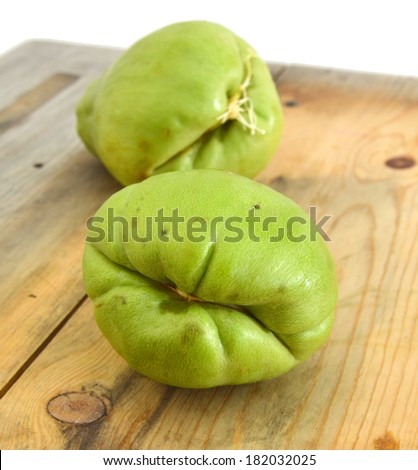 Two chayote squash, also known as christophine, pear-squash, vegetable pear and choko against a wooden board - stock photo