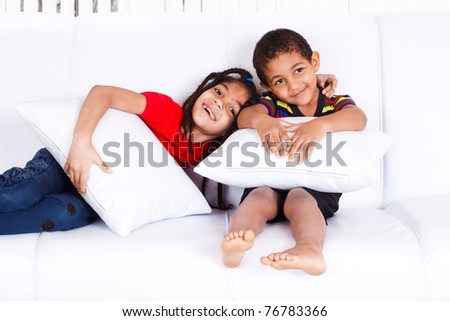 Two cheerful African-American children sitting on the sofa - stock photo