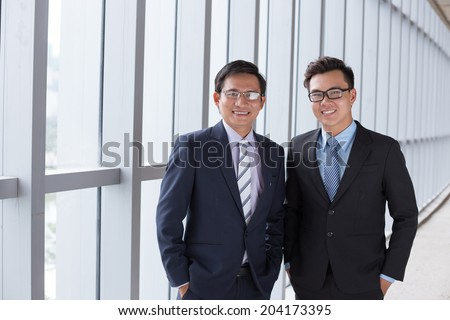 Two cheerful Asian business people: father and son - stock photo