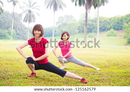 Two cheerful Asian girls stretching outdoor green park - stock photo