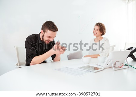 Two cheerful attractive young business people talking and laughing on meeting in the office - stock photo