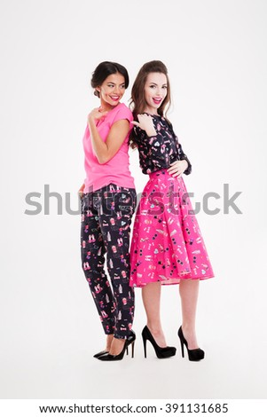 Two cheerful attractive young women standing back to back over white background - stock photo