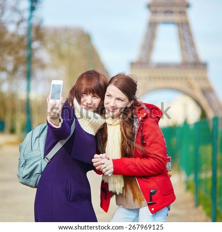 Two cheerful beautiful girls in Paris doing selfi picture (selfie) using mobile phone near the Eiffel tower - stock photo
