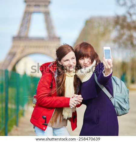 Two cheerful beautiful girls in Paris doing selfie near the Eiffel tower - stock photo