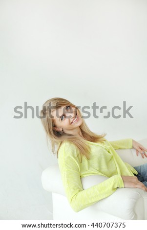 Two cheerful beautiful girls posing for camera inside. Bright makeup, hairdo and casual style. White background, not isolated. - stock photo