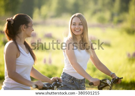 Two cheerful beautiful teenage girls wearing jeans shorts on bicycles in park on sunny summer day, having good time, laughing and chatting, focus on blond young woman - stock photo