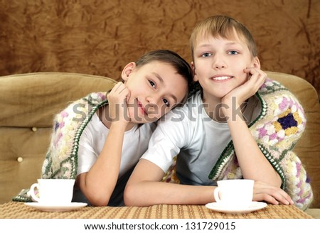 Two cheerful boys drinking tea sheltered rug - stock photo