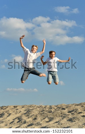 Two cheerful boys jumping against the sky on sand - stock photo