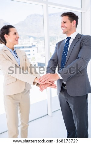Two cheerful business colleagues joining hands together in a bright office
