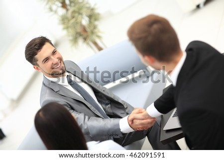 Two cheerful business men shaking hands