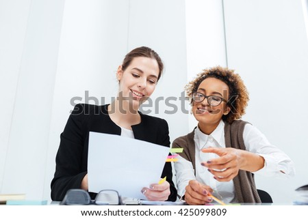 Two cheerful charming businesswomen working with documents together in office - stock photo