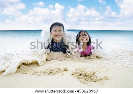 Two cheerful children enjoying holiday at the beach while lying on the sand and playing wave - stock photo