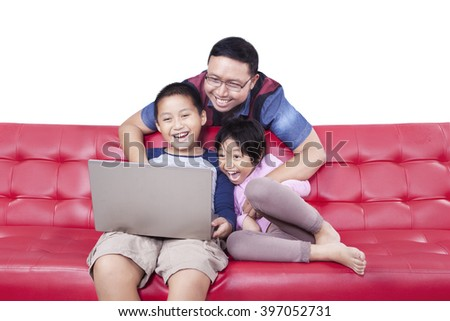 Two cheerful children sitting on the sofa while using laptop computer and laughing together with their father