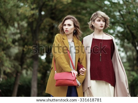 Two cheerful fashion girls  in the autumn park - stock photo