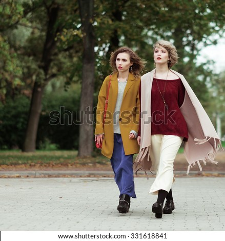 Two cheerful fashion girls  in the autumn park