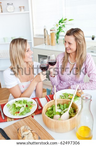 Two cheerful female friends eating salad in the kitchen at home - stock photo