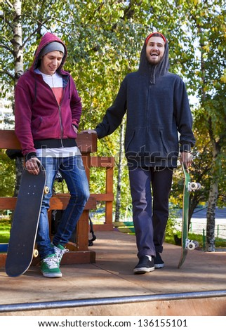 Two cheerful friend skateboarders in the skatepark - stock photo