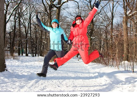 Two cheerful friendly girls jump in park in the winter. - stock photo