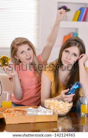 Two cheerful girlfriends spend time together at home